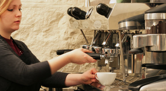 Photograph of a barista making coffee